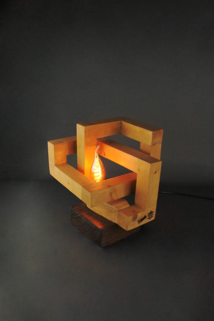 Lampe design en bois géométirque qui s'enroule sur elle-même sur socle en pin foncé avec ampoule LED décorative chaude au centre par SBands Créations orientée à 45°